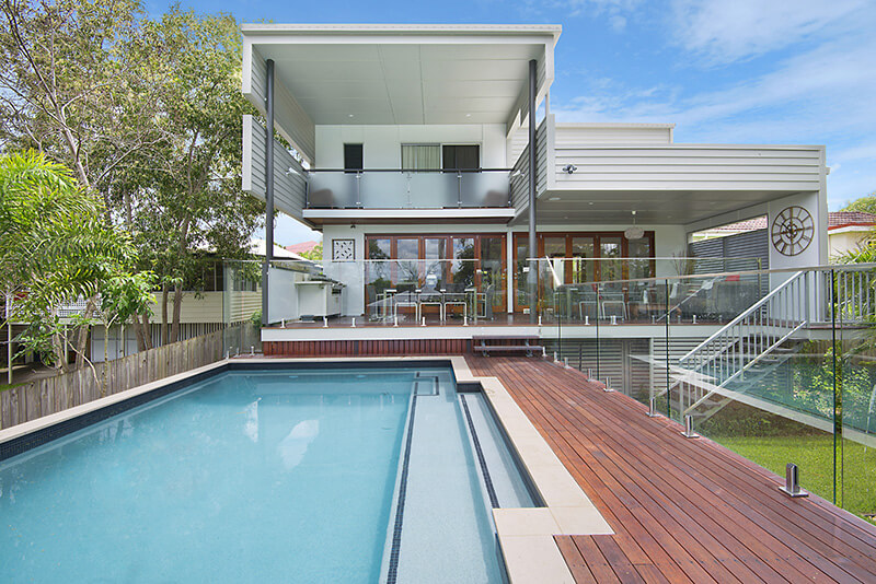 Outdoor pool with deck in front of house