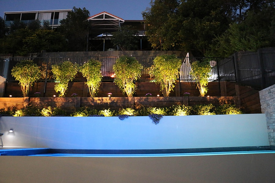 Custom concrete pool with garden lighting at night
