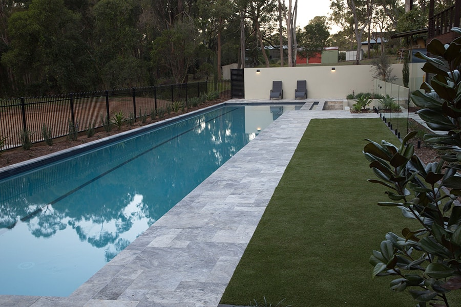 Lap concrete pool with grass and plants
