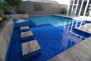 In ground pool with steps and water feature